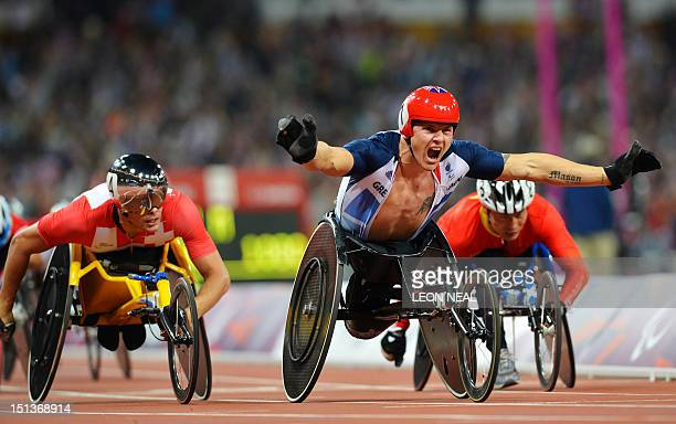 Britain's David Weir celebrates winning gold ahead of Switzerland's Marcel Hug in the men's 800m T54 final during the athletics competition at the...