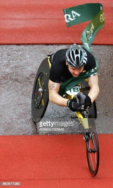 Britain's David Weir crosses the finish line to win the mens wheelchair race during the 26th London Marathon on the Mall in front of Buckingham...