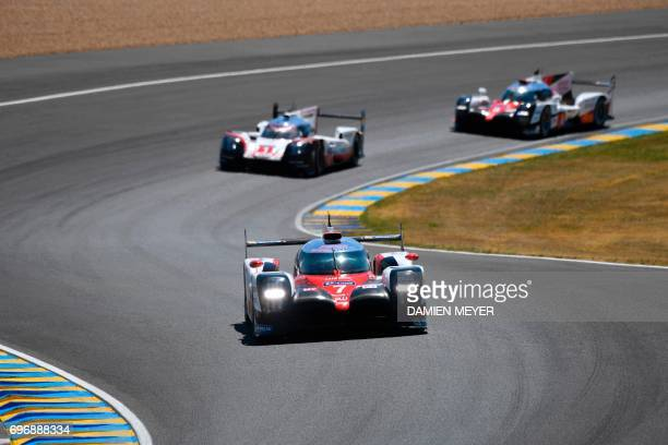 Britain's driver Mike Conway competes on his Toyota TS050 Hybrid N°7 ahead of Switzerland's driver Neel Jani on his Porsche 919 Hybrid N°1 and...