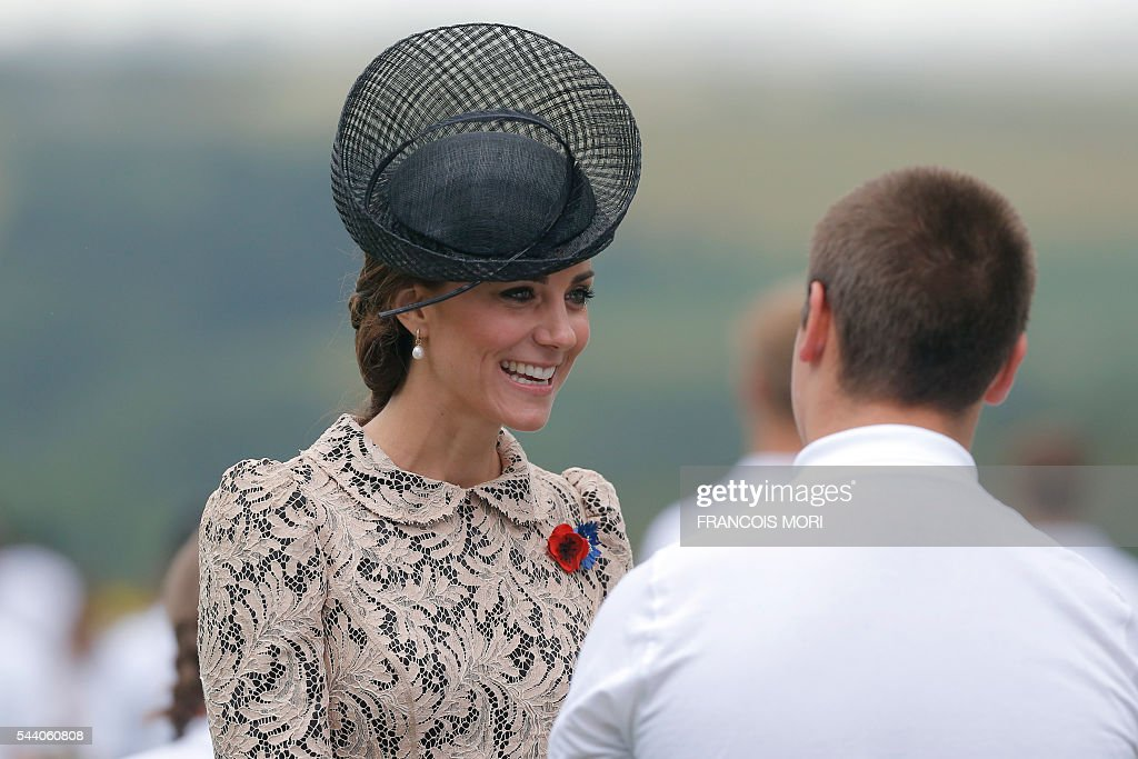 Britain's Duchess Catherine of Cambridge talks with a young volunteer as she attends the memorial ceremony on July 1, 2016, at the Thiepval Memorial in Thiepval, during which Britain and France will mark the 100 years since soldiers emerged from their trenches to begin one of the bloodiest battles of World War I (WWI) at the River Somme. Under grey skies, unlike the clear sunny day that saw the biggest slaughter in British military history a century ago, the commemoration kicked off at the deep Lochnagar crater, created by the blast of mines placed under German positions two minutes before the attack began at 7:30 am on July 1, 1916. / AFP / POOL / Francois Mori