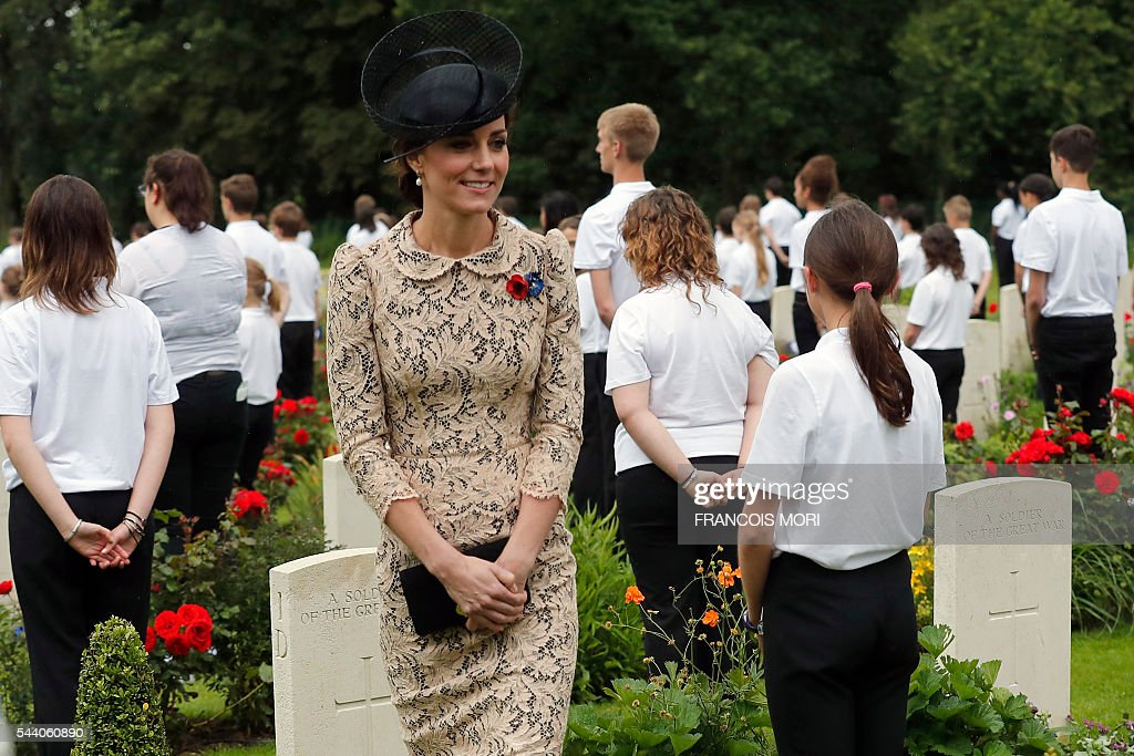 Britain's Duchess Catherine of Cambridge walks among young volunteers in the cemetery of the Thiepval Memorial as she attends the memorial ceremony on July 1, 2016, in Thiepval, during which Britain and France will mark the 100 years since soldiers emerged from their trenches to begin one of the bloodiest battles of World War I (WWI) at the River Somme. Under grey skies, unlike the clear sunny day that saw the biggest slaughter in British military history a century ago, the commemoration kicked off at the deep Lochnagar crater, created by the blast of mines placed under German positions two minutes before the attack began at 7:30 am on July 1, 1916. / AFP / POOL / Francois Mori