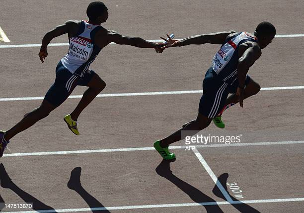 Britain's Dwain Chambers fails to gab the batton from Britain's Christian Malcolm during the men's 4x100m relay final at the 2012 European Athletics...