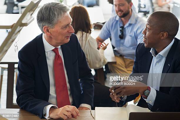 Britain's Finance minister Philip Hammond speaks to a young financial technology entrepeneur during a visit to Barclays Rise a fintech startup hub on...