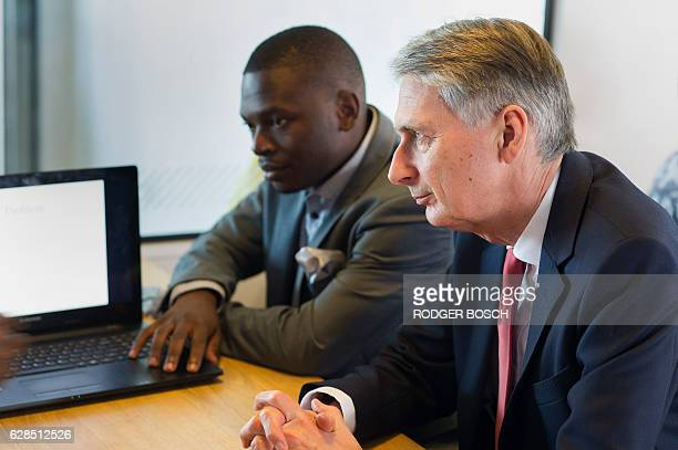 Britain's Finance minister Philip Hammond speaks to young financial technology entrepeneurs during a visit to Barclays Rise a fintech startup hub on...