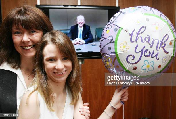 Britain's first successful baby heart transplant patient Kaylee Davidson poses with her mother Carol in front of a video link to her surgeon Chris...