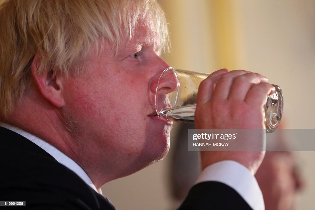 Britain's Foreign minister Boris Johnson sips water during a press conference after his meeting on Libya at Lancaster House in London on September 14, 2017. /