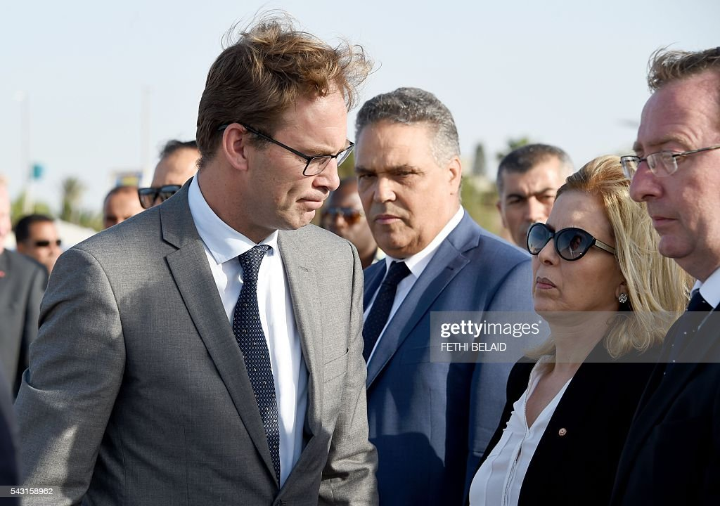 Britain's Foreign Office junior minister, Tobias Ellwood (L), and Tunisia's Tourism Minister, Salma Rekik Elloumi (2nd from R), attend on June 26, 2016, a ceremony in memory of those killed a year ago by a jihadist gunman in front of the Riu Imperial Marhaba Hotel in Port el Kantaoui, on the outskirts of Sousse south of the capital Tunis. Tourists fled in horror on June 26, 2015 as a Tunisian gunman pulled a Kalashnikov rifle from inside a furled beach umbrella and went on a shooting spree outside the five-star hotel. 30 Britons were among 38 foreign holidaymakers killed in the attack. / AFP / FETHI