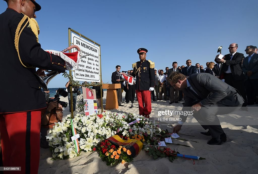 Britain's Foreign Office junior minister, Tobias Ellwood, lays a flower on the beach on June 26, 2016, during a ceremony in memory of those killed a year ago by a jihadist gunman in front of the Riu Imperial Marhaba Hotel in Port el Kantaoui, on the outskirts of Sousse south of the capital Tunis. Tourists fled in horror on June 26, 2015 as a Tunisian gunman pulled a Kalashnikov rifle from inside a furled beach umbrella and went on a shooting spree outside the five-star hotel. 30 Britons were among 38 foreign holidaymakers killed in the attack. / AFP / FETHI