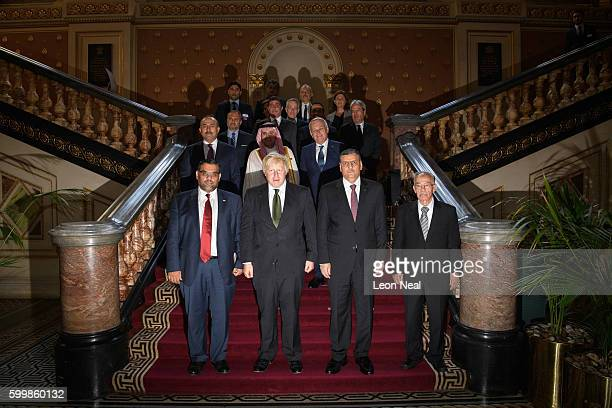 Britain's Foreign Secretary Boris Johnson and Chief Negotiator for the Syrian Opposition Dr Riyad Hijab stand with members of the Syrian High...