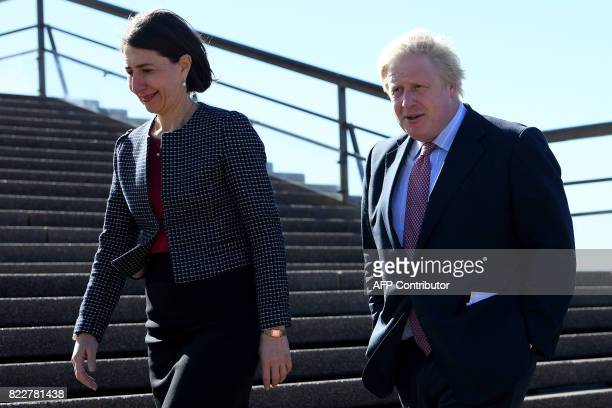 Britain's Foreign Secretary Boris Johnson and New South Wales state premier Gladys Berejiklian walk on the stairs of the Sydney Opera House on July...