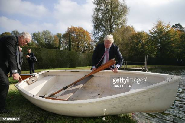 Britain's Foreign Secretary Boris Johnson and Slovenia's State Secretary at the Ministry of Foreign Affairs Andrej Logar lift a small boat to put out...