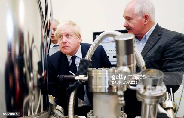 Britain's Foreign Secretary Boris Johnson inspects a scanning tunneling microscope with Professor John Boland during a visit to Trinity College in...