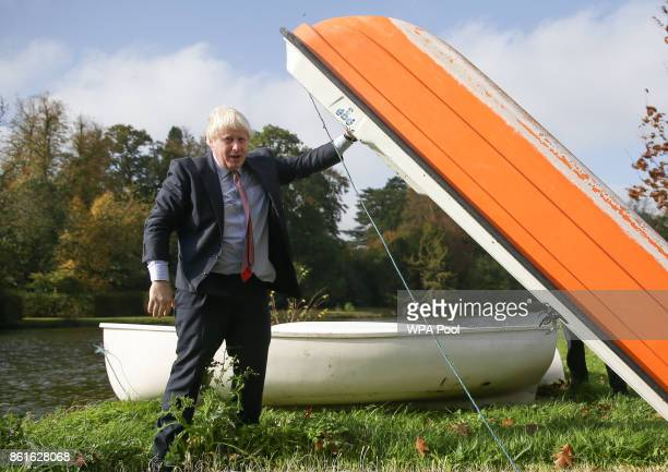 Britain's Foreign Secretary Boris Johnson lifts a small boat before going out onto a boating lake in a rowing boat with Czech Republic's Deputy...