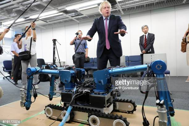 Britain's Foreign Secretary Boris Johnson looks at the OCTOPUS Disaster response robot at the Research Institute for Science and Engineering at...