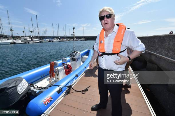 Britain's Foreign Secretary Boris Johnson prepares to board a boat to inspect the British Olympic sailing team in Hayama Kanagawa prefecture on July...