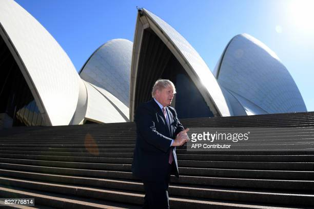 Britain's Foreign Secretary Boris Johnson walks on the stairs of the Sydney Opera House after poses for photos in Sydney on July 26 2017 Johnson is...