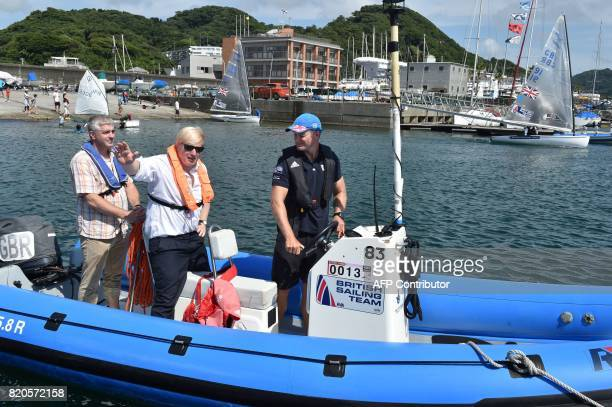 Britain's Foreign Secretary Boris Johnson waves from a boat during his inspection of the British Olympic sailing team in Hayama Kanagawa prefecture...