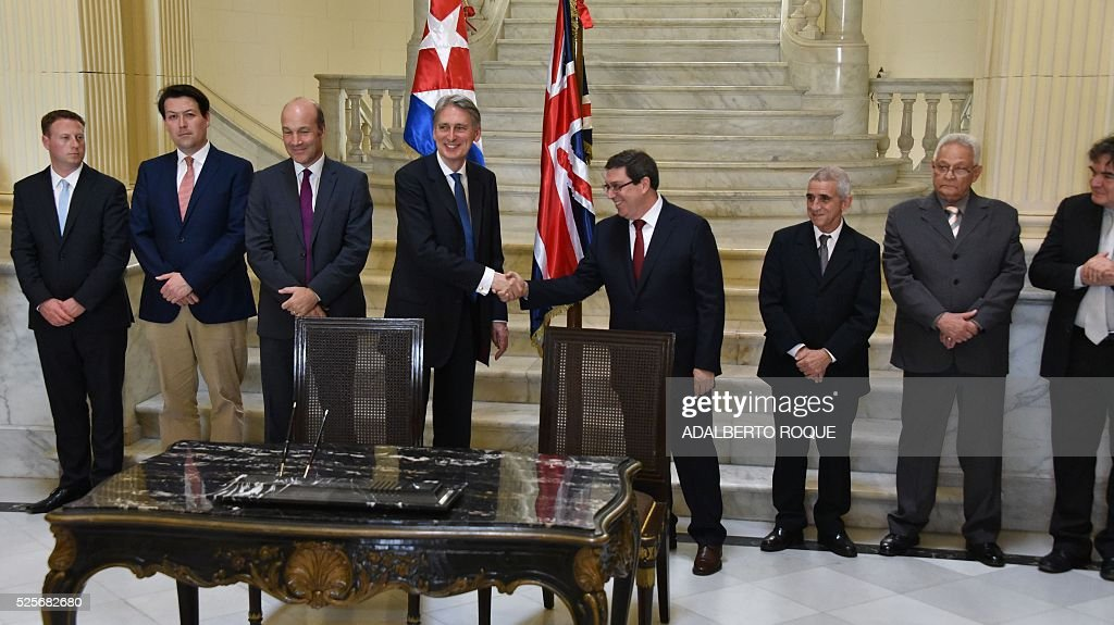 Britain's Foreign Secretary Philip Hammond (4-L) shakes hands with his Cuban counterpart Bruno Rodriguez (C-R) at the Foreign Affairs Ministry in Havana on April 28, 2016. Hammond arrived in Cuba on Thursday in the first such visit since 1959, to hold talks on cooperation in 'financial services, energy, culture and education', London announced. / AFP / ADALBERTO