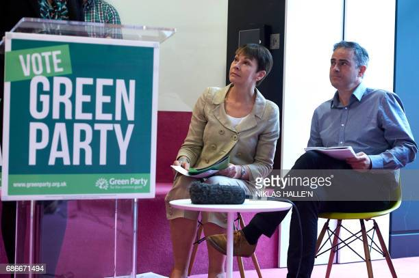 Britain's Green Party coleaders Caroline Lucas and Jonathan Bartley listen to a speech during the launch the Green Party's 'Green Guarantee' of key...