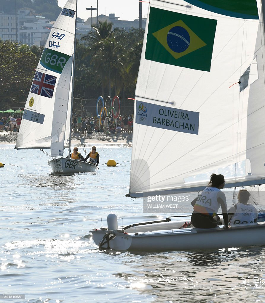 Britain's Hannah Mills and Saskia Clark and Brazil's Fernanda Oliveira and Ana Luiza Barbachan wait for the wind to compete in the 470 Women medal...