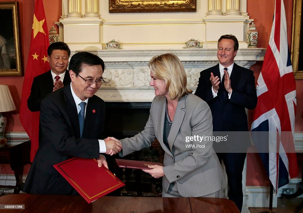 Britain's International Development Secretary <a gi-track='captionPersonalityLinkClicked' href=/galleries/search?phrase=Justine+Greening&family=editorial&specificpeople=2466449 ng-click='$event.stopPropagation()'>Justine Greening</a> (front R) and China's Minister of Commerce Gao Hucheng shake hands after signing an agreement as Britain's Prime Minister <a gi-track='captionPersonalityLinkClicked' href=/galleries/search?phrase=David+Cameron+-+Politician&family=editorial&specificpeople=227076 ng-click='$event.stopPropagation()'>David Cameron</a> (R) and China's President <a gi-track='captionPersonalityLinkClicked' href=/galleries/search?phrase=Xi+Jinping&family=editorial&specificpeople=2598986 ng-click='$event.stopPropagation()'>Xi Jinping</a> applaud in 10 Downing Street on October 21, 2015 in London, England. The President of the Peoples Republic of China, Mr <a gi-track='captionPersonalityLinkClicked' href=/galleries/search?phrase=Xi+Jinping&family=editorial&specificpeople=2598986 ng-click='$event.stopPropagation()'>Xi Jinping</a> and his wife, Madame Peng Liyuan, are paying a State Visit to the United Kingdom as guests of The Queen. They will stay at Buckingham Palace and undertake engagements in London and Manchester. The last state visit paid by a Chinese President to the UK was Hu Jintao in 2005.