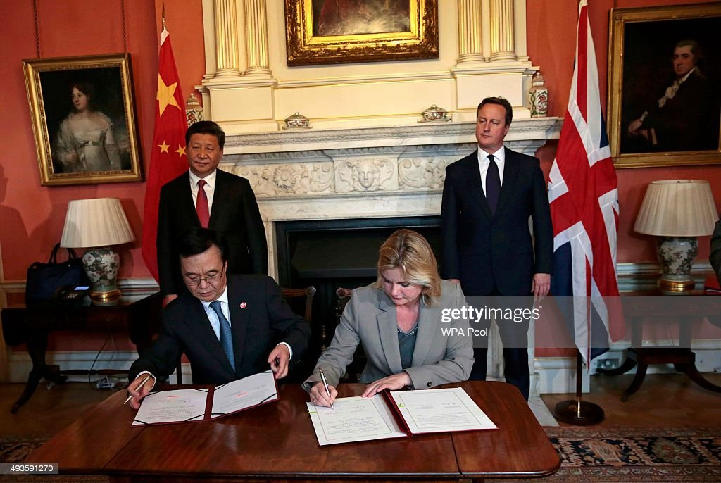 Britain's International Development Secretary Justine Greening (front R) and China's Minister of Commerce Gao Hucheng sign an agreement as Britain's Prime Minister David Cameron (R) and China's President Xi Jinping applaud in 10 Downing Street on October 21, 2015 in London, England. The President of the Peoples Republic of China, Mr Xi Jinping and his wife, Madame Peng Liyuan, are paying a State Visit to the United Kingdom as guests of The Queen. They will stay at Buckingham Palace and undertake engagements in London and Manchester. The last state visit paid by a Chinese President to the UK was Hu Jintao in 2005.