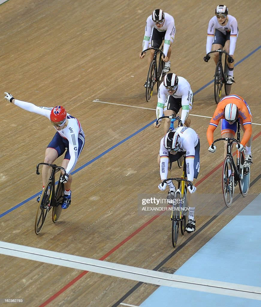 Britain's Jason Kenny (L) crosses a finish line winning the gold in Men's Keirin event, followed by German Maximilian Levy and Dutch Matthijs Buchli during the UCI Track Cycling World Championships in Minsk on February 22, 2013 AFP PHOTO / ALEXANDER NEMENOV