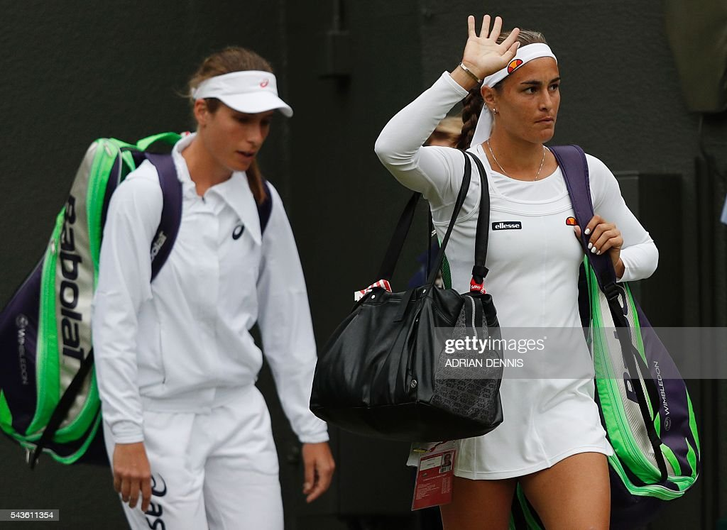 Britain's Johanna Konta (L) and Puerto Rico's Monica Puig arrive on court for their women's singles first round match on the third day of the 2016 Wimbledon Championships at The All England Lawn Tennis Club in Wimbledon, southwest London, on June 29, 2016. / AFP / ADRIAN