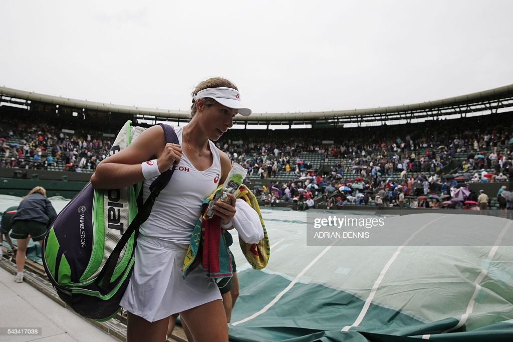 Britain's Johanna Konta leaves No 1 Court as the rain covers are put on stopping her women's singles first round match against Puerto Rico's Monica Puig on the second day of the 2016 Wimbledon Championships at The All England Lawn Tennis Club in Wimbledon, southwest London, on June 28, 2016. / AFP / ADRIAN