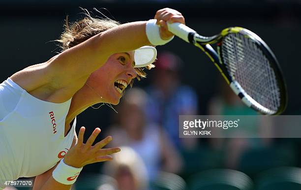 Britain's Johanna Konta serves to Russia's Maria Sharapova during their women's singles first round match on day one of the 2015 Wimbledon...