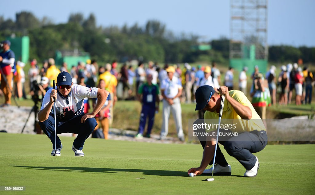 Britain's Justin Rose watches Sweden's Henrik Stenson preparing to put for Bogey on the 18th in the men's individual stroke play final day at the...