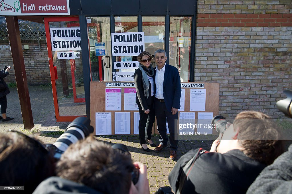 Britain's Labour party candidate for London Mayor Sadiq Khan (R) and his wife Saadiya pose for photographers as they leave a Polling Station in south London on May 5, 2016, after casting their votes. Londoners go to the polls on Thursday to elect their new mayor following a bitter campaign between the two leading candidates Khan, and Conservative Zac Goldsmith, that stayed ugly to the very end. / AFP / JUSTIN