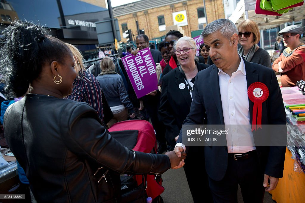 Britain's Labour party candidate for London Mayor Sadiq Khan (R), canvasses for supporters at a market in London on May 4, 2016, on the eve of the London mayoral elections. Londoners choose their new mayor on May 5, 2016, after a straight fight between rival candidates Zac Goldsmith and Sadiq Khan dominated by negative campaigning. / AFP / JUSTIN