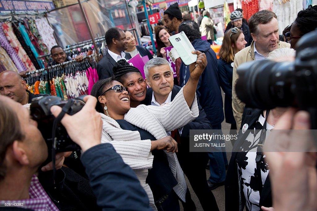 Britain's Labour party candidate for London Mayor Sadiq Khan (C right), poses for a 'selfie' photograph while canvassing for supporters at a market in London on May 4, 2016, on the eve of the London mayoral elections. Londoners choose their new mayor on May 5, 2016, after a straight fight between rival candidates Zac Goldsmith and Sadiq Khan dominated by negative campaigning. / AFP / JUSTIN