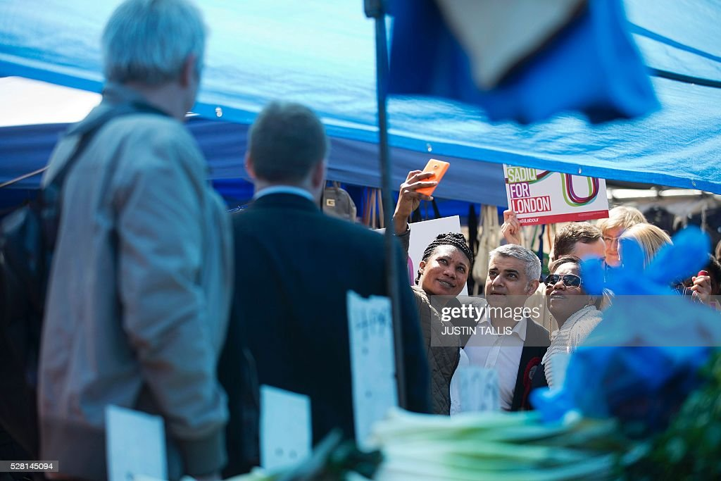 Britain's Labour party candidate for London Mayor Sadiq Khan poses for a 'selfie' photograph while canvassing for supporters at a market in London on May 4, 2016, on the eve of the London mayoral elections. Londoners choose their new mayor on May 5, 2016, after a straight fight between rival candidates Zac Goldsmith and Sadiq Khan dominated by negative campaigning. / AFP / JUSTIN