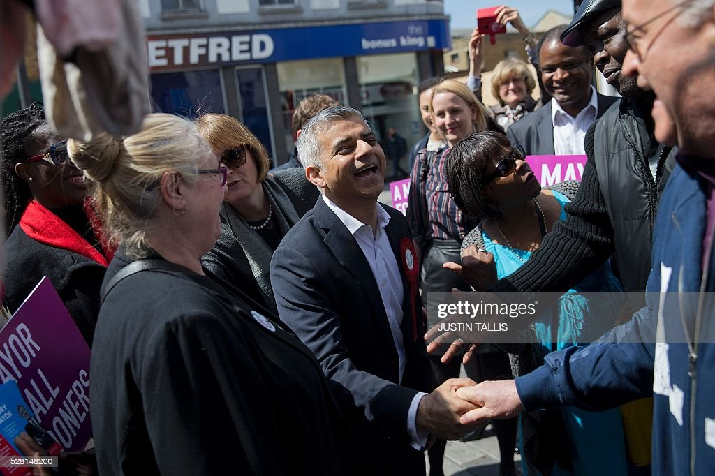 Britain's Labour party candidate for London Mayor Sadiq Khan (C), reacts as he canvasses for supporters at a market in London on May 4, 2016, on the eve of the London mayoral elections. Londoners choose their new mayor on May 5, 2016, after a straight fight between rival candidates Zac Goldsmith and Sadiq Khan dominated by negative campaigning. / AFP / JUSTIN