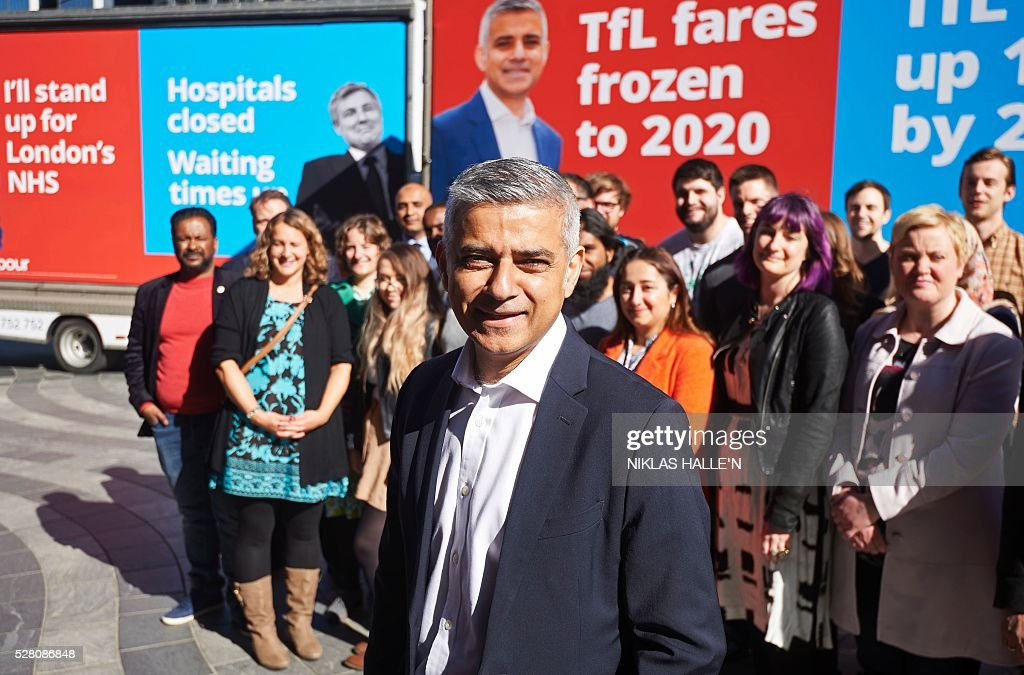 Britain's Labour party candidate for London Mayor Sadiq Khan (C), unveils a poster campaign in Canary Wharf, east London on May 4, 2016, on the eve of the London mayoral elections. Londoners choose their new mayor on May 5, 2016, after a straight fight between rival candidates Zac Goldsmith and Sadiq Khan dominated by negative campaigning. / AFP / Niklas HALLE'N