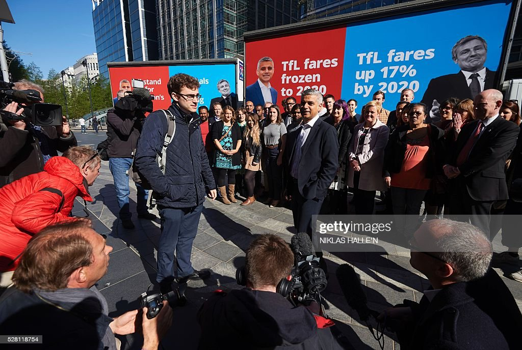 Britain's Labour party candidate for London Mayor Sadiq Khan (C right), unveils a poster campaign in Canary Wharf, east London on May 4, 2016, on the eve of the London mayoral elections. Londoners choose their new mayor on May 5, 2016, after a straight fight between rival candidates Zac Goldsmith and Sadiq Khan dominated by negative campaigning. / AFP / NIKLAS HALLE'N