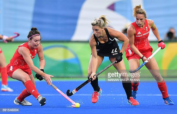 Britain's Laura Unsworth and Britain's Susannah Townsend vie with New Zealand's Gemma Flynn during the women's semifinal field hockey New Zealand vs...