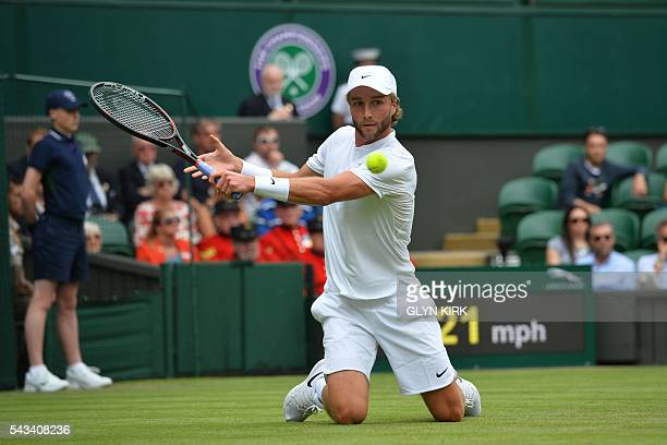 TOPSHOT Britain's Liam Broady plays a shot from his knees after slipping against Britain's Andy Murray during their men's singles first round match...