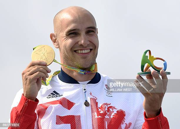 Britain's Liam Heath celebrates on the podium of the Men's Kayak Single 200m final at the Lagoa Stadium during the Rio 2016 Olympic Games in Rio de...