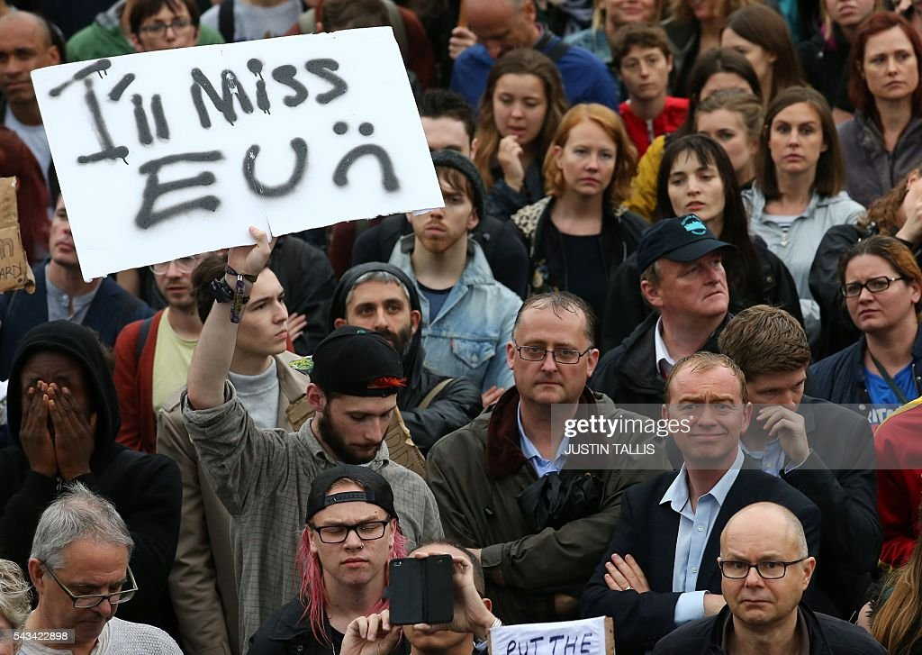 Britain's Liberal Democrats Party leader Tim Farron (below right, blue shirt) joins people at an anti-Brexit protest in Trafalgar Square in central London on June 28, 2016. EU leaders attempted to rescue the European project and Prime Minister David Cameron sought to calm fears over Britain's vote to leave the bloc as ratings agencies downgraded the country. Britain has been pitched into uncertainty by the June 23 referendum result, with Cameron announcing his resignation, the economy facing a string of shocks and Scotland making a fresh threat to break away. / AFP / JUSTIN