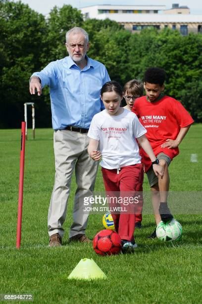 Britain's main opposition Labour party leader Jeremy Corbyn coaches children during a visit to Hackney Marshes football pitches in London on May 27...