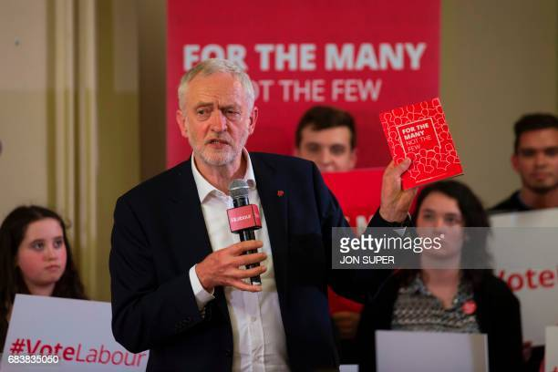 Britain's main opposition Labour Party leader Jeremy Corbyn holds up the party manifesto as he speaks at a general election rally at Swinnow...