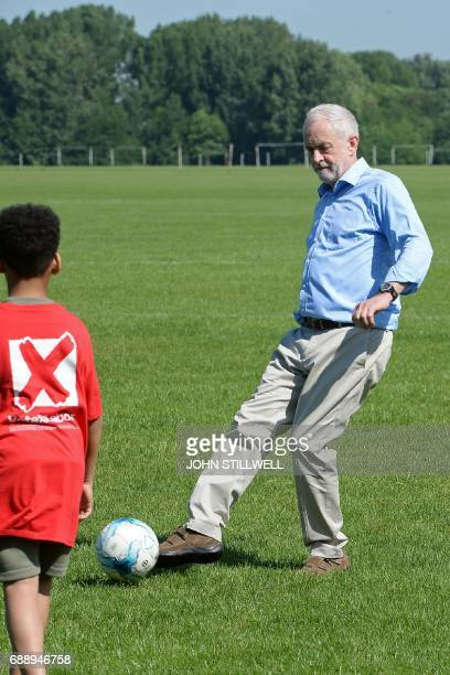 Britain's main opposition Labour party leader Jeremy Corbyn passes the ball as he plays football with children during a visit to Hackney Marshes...