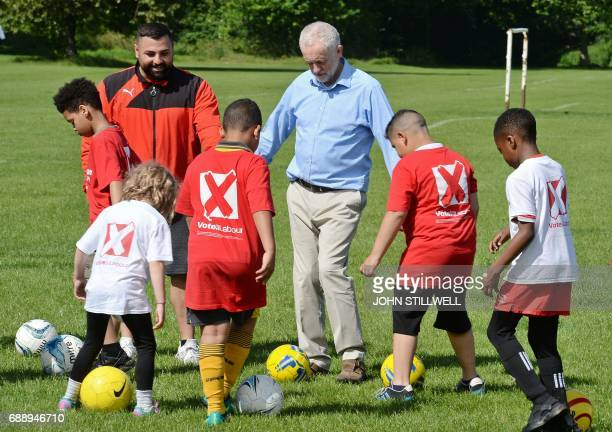 Britain's main opposition Labour party leader Jeremy Corbyn plays football with children during a visit to Hackney Marshes football pitches in London...