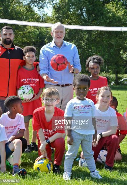 Britain's main opposition Labour party leader Jeremy Corbyn poses for a photograph with children during a visit to Hackney Marshes football pitches...