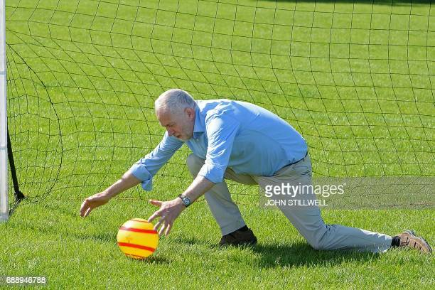 Britain's main opposition Labour party leader Jeremy Corbyn saves a penalty kick as he plays football with children during a visit to Hackney Marshes...
