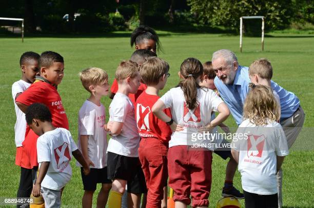 Britain's main opposition Labour party leader Jeremy Corbyn speaks to children during a visit to Hackney Marshes football pitches in London on May 27...