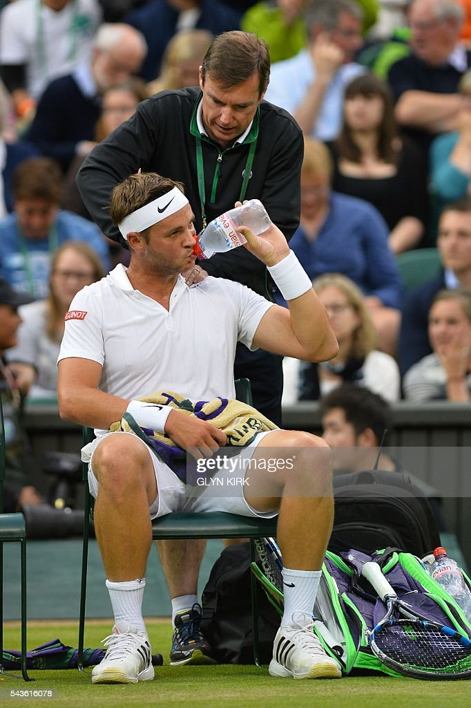 Britain's Marcus Willis gets a massage in the break between games against Switzerland's Roger Federer in their men's singles second round match on the third day of the 2016 Wimbledon Championships at The All England Lawn Tennis Club in Wimbledon, southwest London, on June 29, 2016. / AFP / GLYN